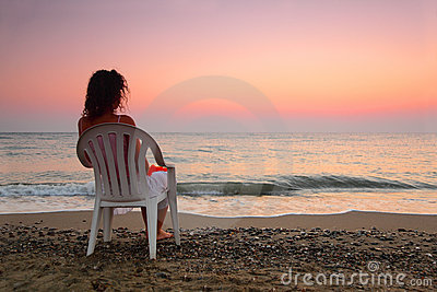 Woman sitting on plastic chair on beach