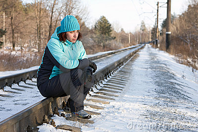The woman sitting on rails of the railway
