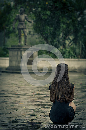 Woman sitting in the rain, with little black dress