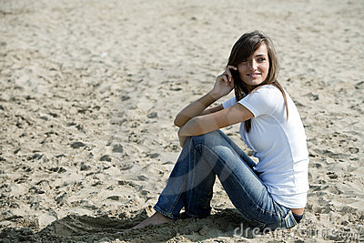 Woman sitting in the sand with a mobile phone