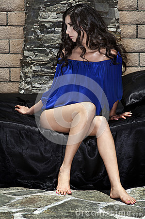 Woman sitting on satin bed