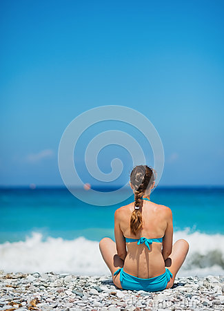 Woman sitting on sea shore
