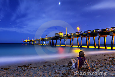 Woman sitting on shore at night