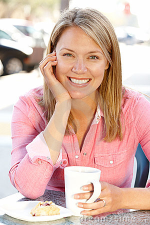 Woman sitting at sidewalk cafe