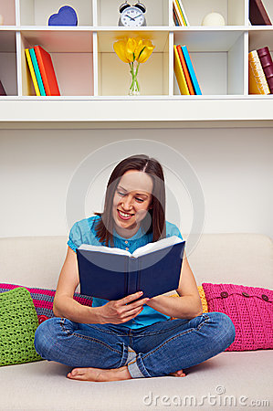 Woman sitting on sofa and reading the book