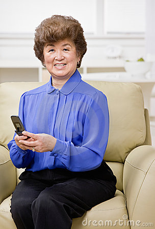 Woman sitting on sofa text messaging