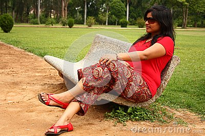 Woman sitting on stone bench in a park