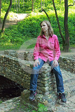 A woman sitting on a stone bridge parapet