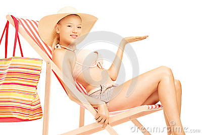 Woman sitting on a sun lounger and gesturing with a hand