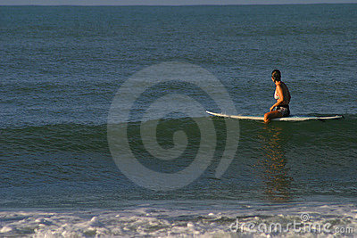 Woman Sitting on Surfboard