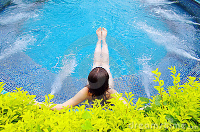 Woman sitting in swimming pool
