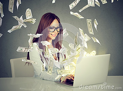 Woman sitting at table using working on a laptop computer making money Stock Photo