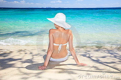 Woman sitting at tropical sea shore.