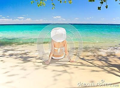 Woman sitting at tropical sea shore.