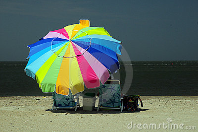 Woman sitting under colorful umbrella