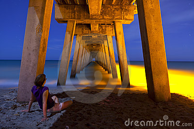 Woman sitting under pier at night