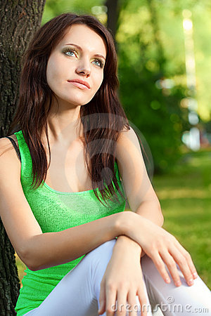 Woman sitting under the tree and dreaming