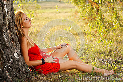 Woman sitting under tree in park