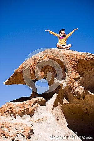 Woman sitting on volcanic rock