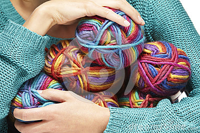 Woman sitting with yarn rolls in her arms Stock Photo