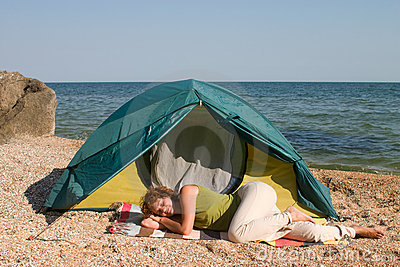 Woman sleep near of tent at seaside