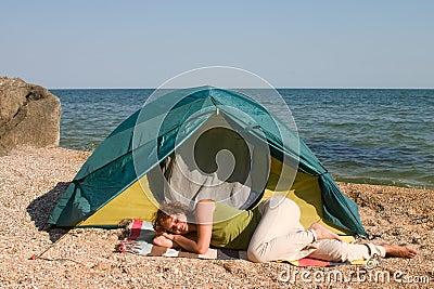 Woman sleep near of tent at seaside