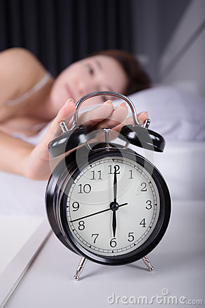 Free Woman Sleeping And Wake Up To Turn Off The Alarm Clock In Mornin Stock Photography - 93457732