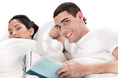 Woman sleeping and man happily reading book in bed
