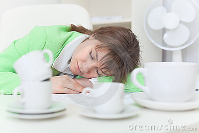 Woman sleeps on table among coffee cups