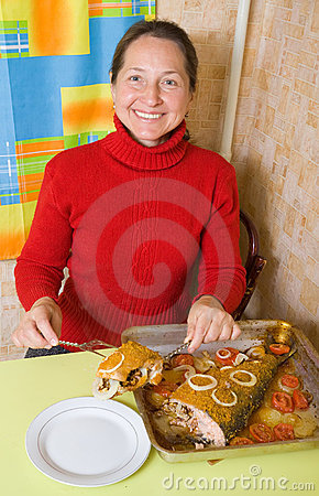 Woman slicing breaded fish