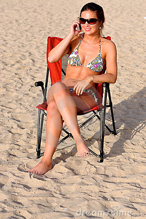 Woman with smartphone calling at the beach