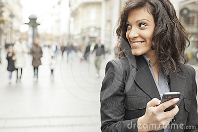 Woman with smartphone in hands walking on street