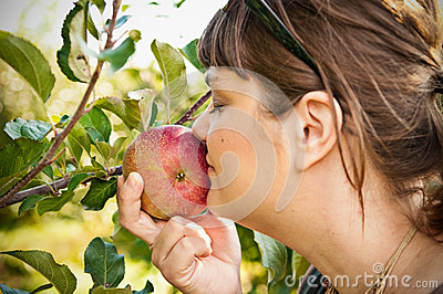 Woman Smelling An Apple On A Tree