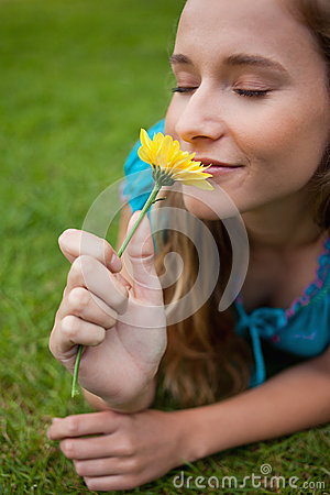 Woman smelling a flower while lying on the grass