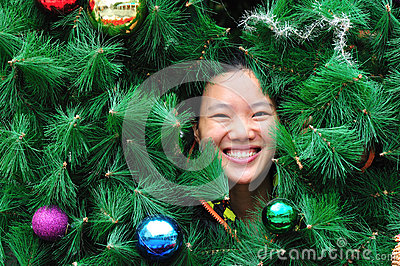 Woman smile behind christmas tree