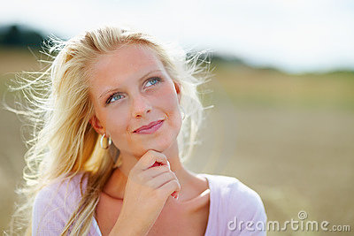 Woman smiling against an open farm , looking away