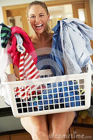 Woman Smiling At Camera With Laundry Basket