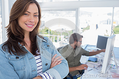 Woman smiling in creative office with arms folde