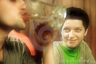 Woman smiling at man drinking