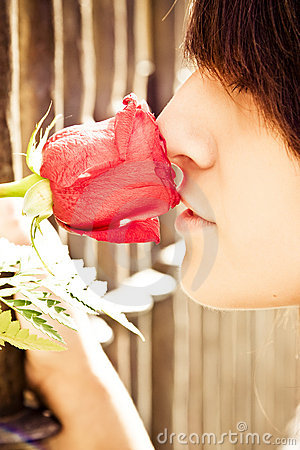 Woman smiling rose behind fence
