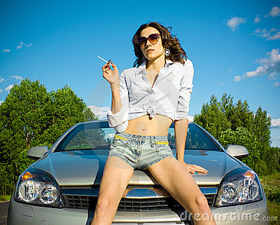 Woman is smoking on a car hood
