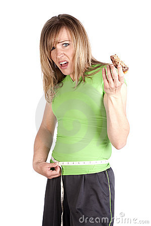Woman with snack measuring waist unhappy