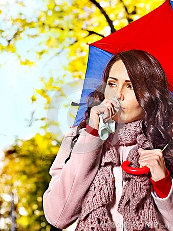 Woman sneezing handkerchief outdoor.