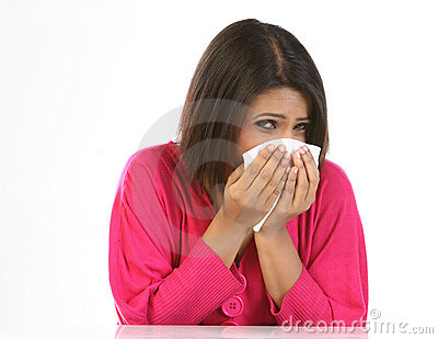 Woman sneezing to a paper handkerchief