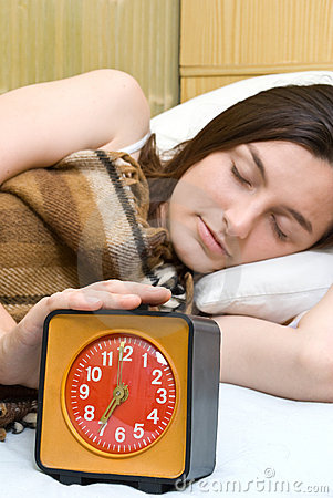 Woman snoozing a red alarm clock