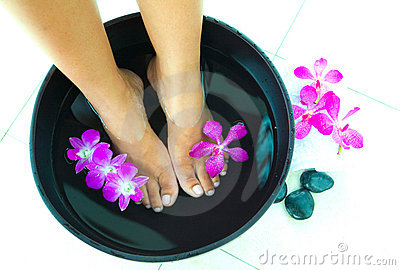 Woman soaking feet in bowl of water