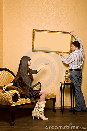 Woman on sofa and man hang up on wall picture