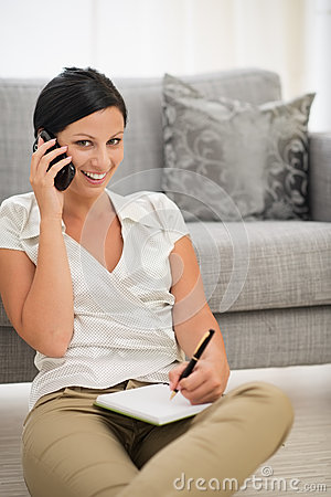 Woman speaking cell phone and writing in notebook