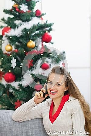 Woman speaking mobile phone near Chris(tmas tree
