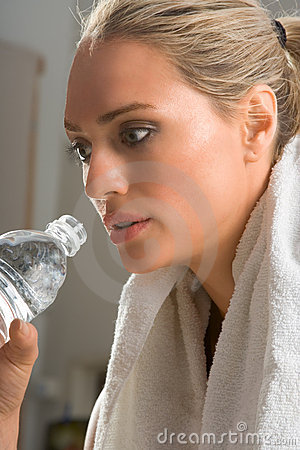 woman with sport drink and towel around in gym